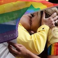 Två personer kysser varandra bakom en regnbågsflagga.