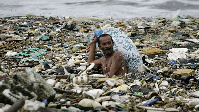 En filipinsk man samlar plast som drivit i land.