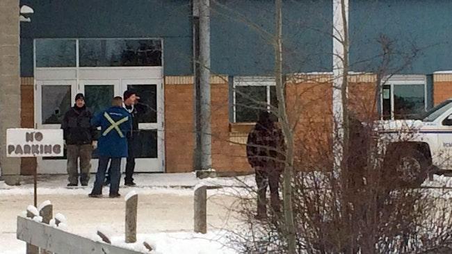 Personer står utanför La Loche Community School i Kanada.