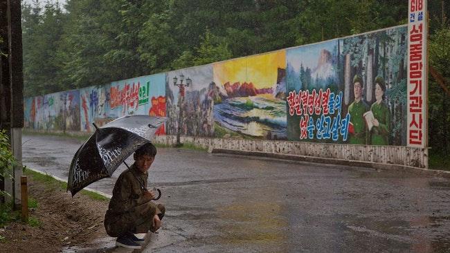 En man söker skydd i regnet i Samjiyon, som ligger i Ryanggang-provinsen i Nordkorea.