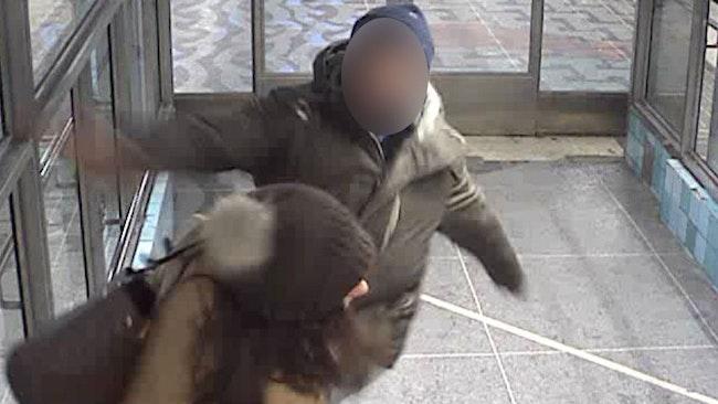 Mannen slår kvinnan i ansiktet med knuten näve medan hon skyddar barnen.