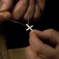 Guldsmed Anders Olsson har gjort ett kors och sätter i kedjan.
