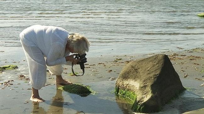 Ulla Lundegård fotograferar på stranden.