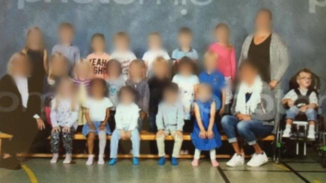 Elis sitter i sin rullstol till höger i bild. Resten av klassen sitter till vänster i en grupp.