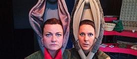 Två kvinnor med varsin vagina på huvudet