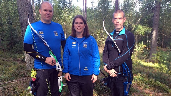 två män och en kvinna i träningskläder, med pilbågar, i skogen