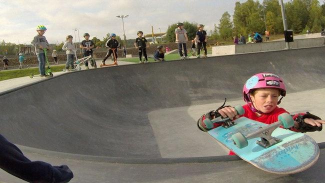 barn på kanten av bowl i skatepark, en pojke som klättrar upp