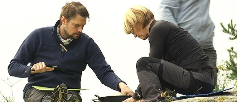 man och kvinna i friluftskläder sitter och pysslar med mat på en klipphäll