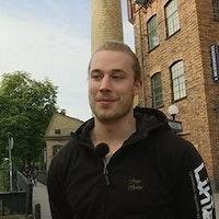 Jesper Rosenberg står framför en tegelbyggnad.