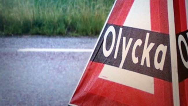 Skylt om trafikolycka utställd på en väg. Gräs i bakgrunden.