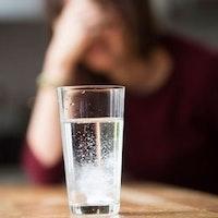 Kvinna med huvudvärk och ett glas med Treo.