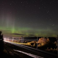 Järnvägsspår och träd i förgrunden. Norrsken mot stjärnrik natthimmel.