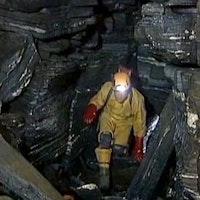 Man med pannlampa undersöker grotta