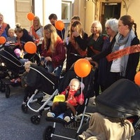Föräldrar och barn och barnvagnar utan för Olaus Petri församlingshem.