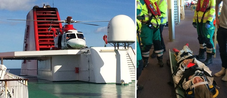 """Räddnignshelikopter som landat på färja. Statist som ligger """"skadad"""" på bår med räddningspersonal omkring sig."""