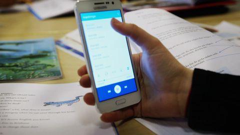 En elev håller i en mobil i ett klassrum.