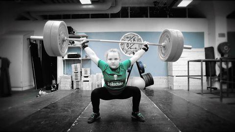 Amelie lyfter vikter i träningslokalen.