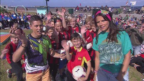 Alex och Malin framför fotbollsspelande Sommarlovsbesökare.