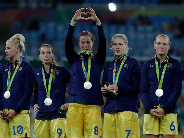 Lotta Schelin gör ett hjärta under prisutdelningen efter OS-finalen i fotboll, omgiven av lagkamraterna
