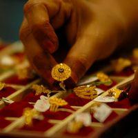 En smyckesspekulant väljer bland guldringar i indiska Gauhati, 14 mars 2008.