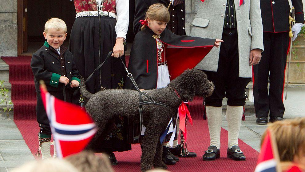 Prins Sverre Magnus, prinsessan Ingrid Alexandra och kronprinsfamiljens hund Milly Kakao hälsar på barntåget utanför Skaugum