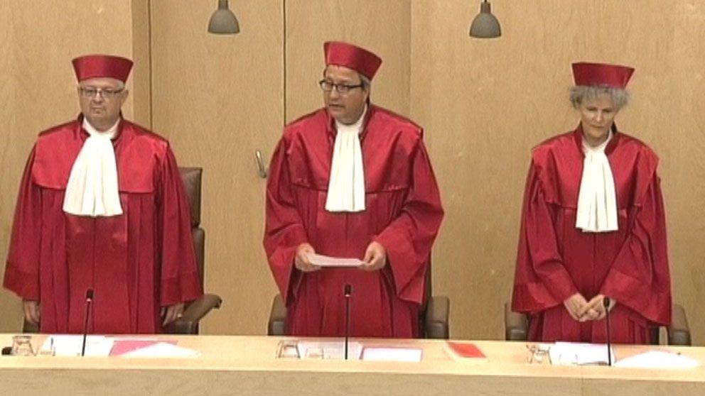 Tre rödklädda domare står upp varav en presenterar domen. Foto: Reuters.