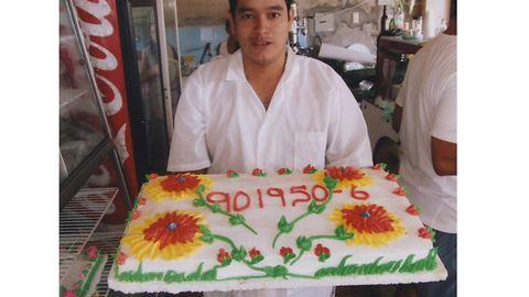 Man som håller fram en stor tårta med Radiohjälpens pg nummer 90 1950-6.