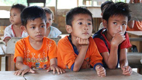 Tre pojkar sitter vid en skolbänk Aceh/Indonesien.