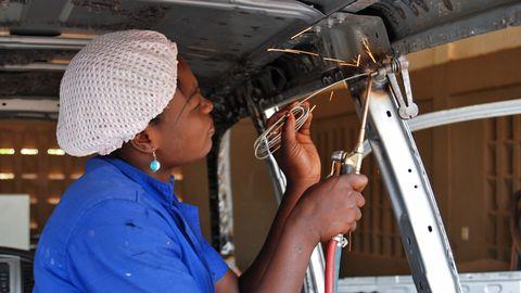 Ung kvinna som svetsar i en bilkaross Burkina Faso.