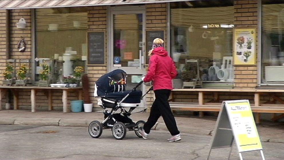 kvinna går med barnvagn