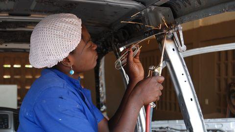 Ung kvinna i blå arbetskläder svetsar på insidan av en bil.