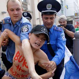 Ukrainsk polis griper en Femenaktivist som protesterar mot den ryska presidenten Vladimir Putin.