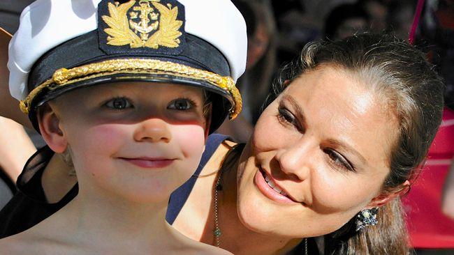 Jamie 7 år provar en stor hatt med hjälp av Kronprinsessan Victoria.