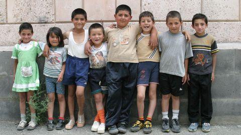 Barn framför en tegelmur.