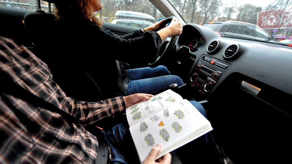Flicka övningskör bil med lärare bredvid sig