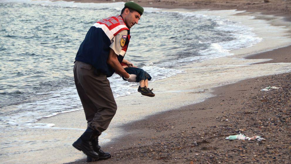 En turkisk militärpolis bär bort den döda pojken.