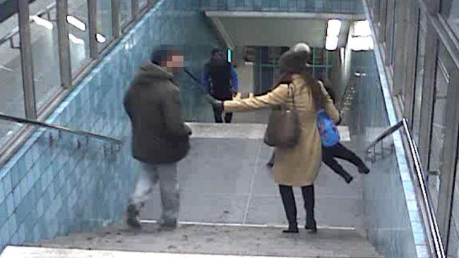 Mannen spottar kvinnan i ansiktet när hon bär sitt barn.