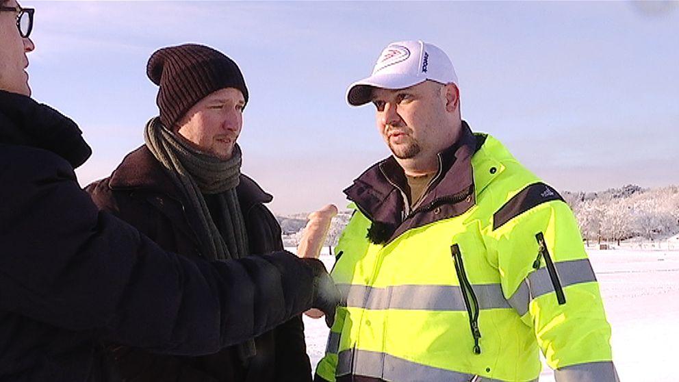 Reporter håller dildo som mikrofon. Två män på saneringsfirma svarar på reporterns frågor.