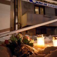 Tända ljus i snö framför polisavspärrning