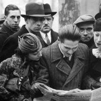 Människor läser över axeln på en man som har en tidning, Paris, 1934.