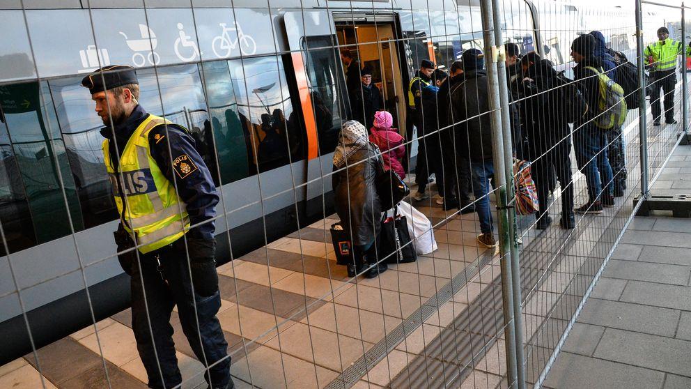 Flyktingar kliver av tåget bakom det nya staketet efter id-kontroller i Malmö.