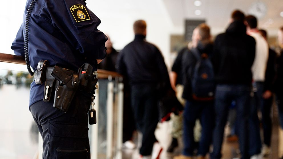 En polis står och och bevakar en rättegång i Södertörns tingsrätt.