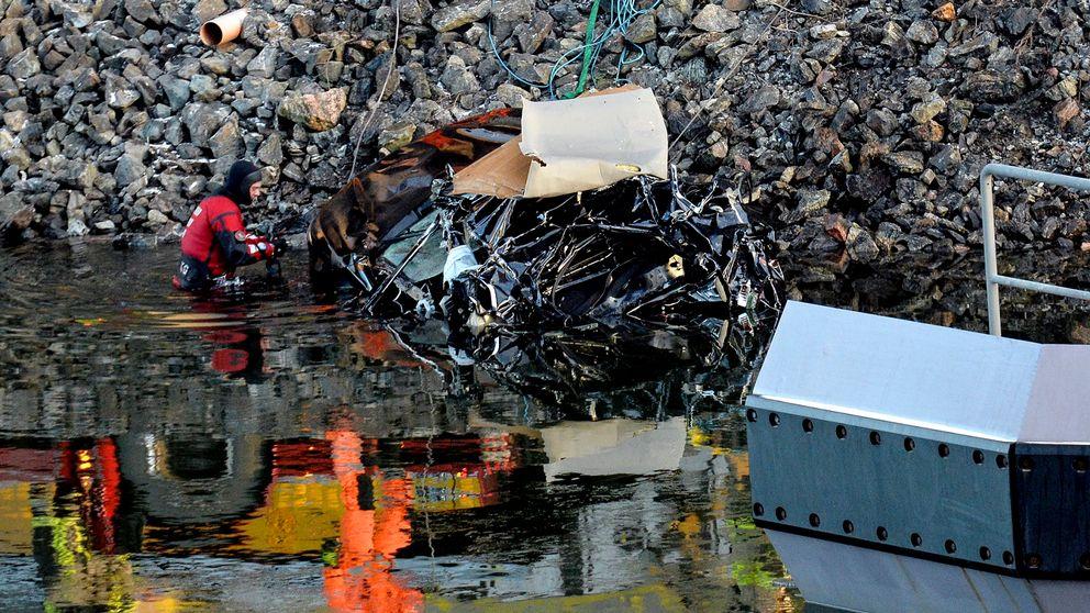 Olycksbilen bärgas vid olycksplatsen och dykare letar i vattnet runt bilen.