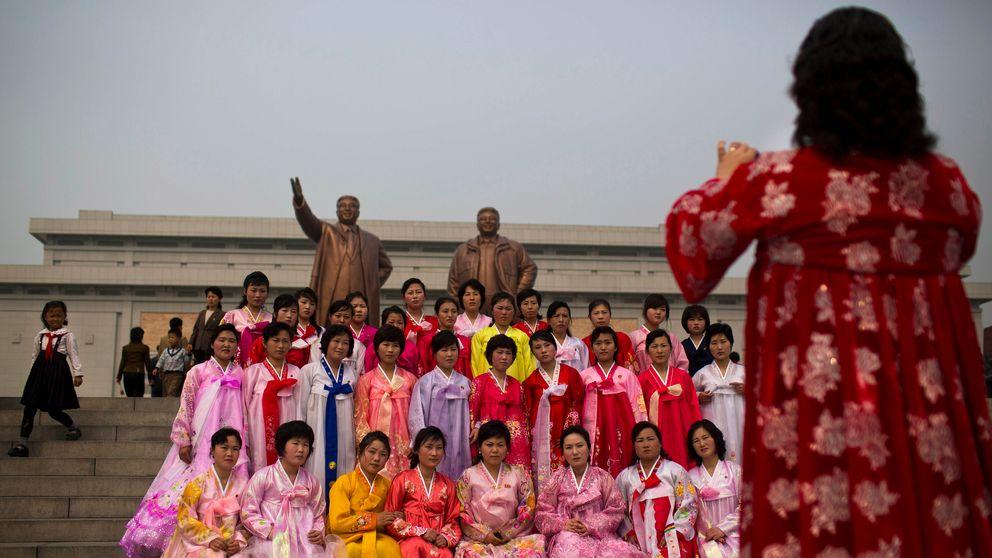 Kvinnor poserar framför statyer av Kim Il Sung and Kim Jong Il på Munsu Hill i Pyongyang.