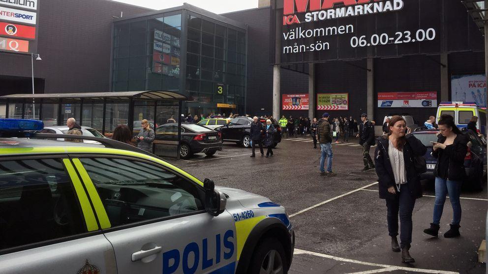 Polisbil och människor utanför allums köpcentrum.