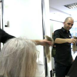 Frisören håller upp Lars-Ove Löfs avklippta hår.