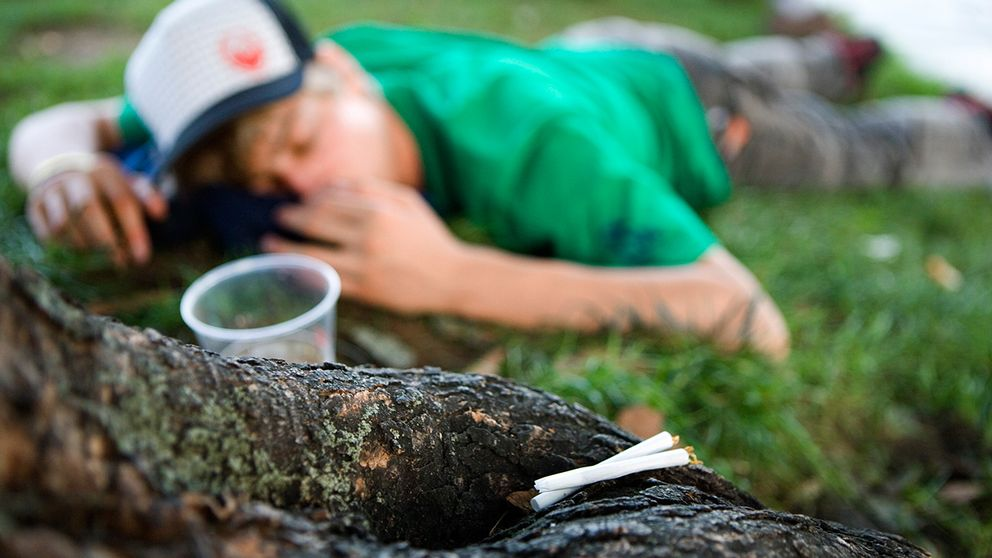 Ung kille sover bredvid en öl.