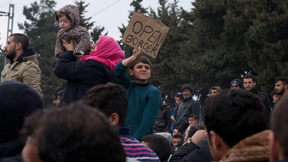 """Flyktingar håller upp en skylt med texten """"Open border""""."""