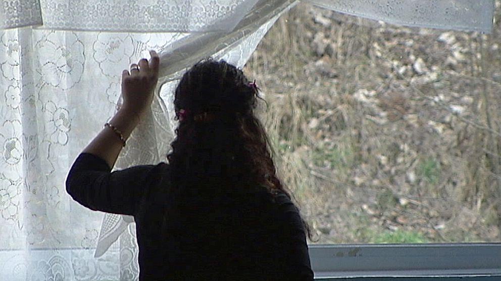 Kvinna tittar ut genom fönster
