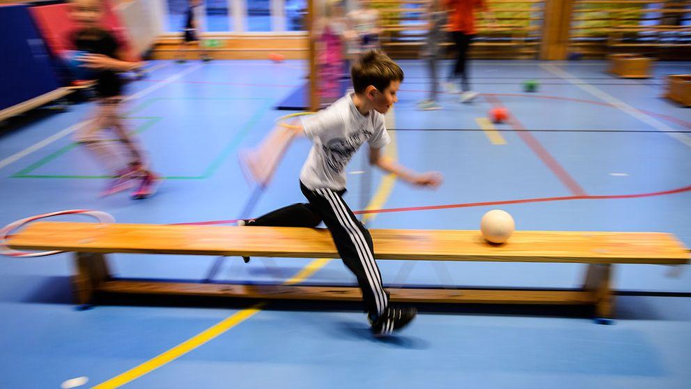 Pojke springer med boll i gymnastiksal.